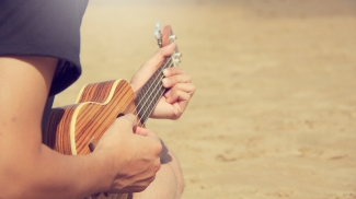 A man playing ukulele on the sandy beach in close up view. travel concept
